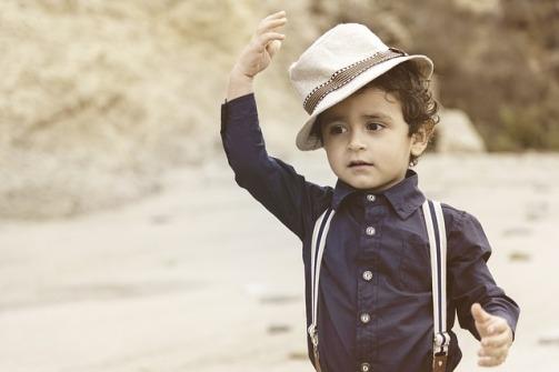 Niño vestido de forma elegante con camisa, tirantes y gorra.jpg