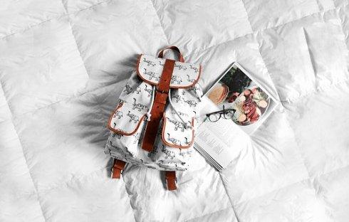 collage de mochila blanca con revista y gafas de ver