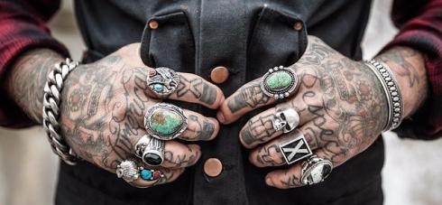 imagen de manos tatuadas con anillos