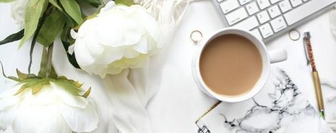 imagen de un escritorio blanco con flores y una taza de café