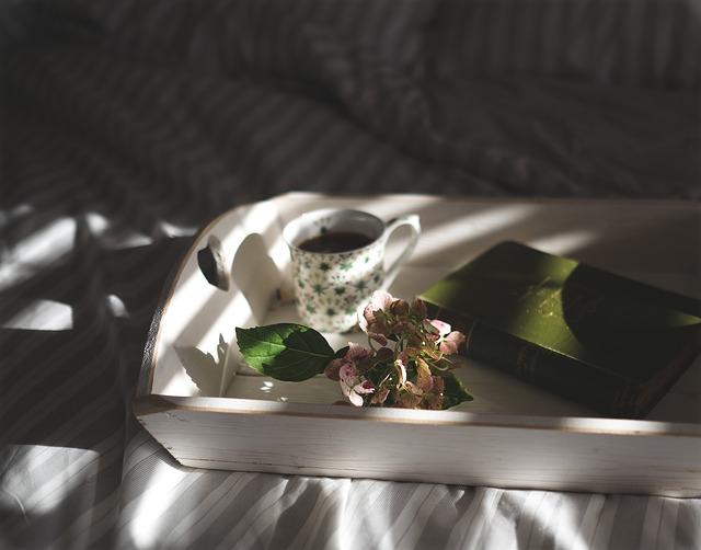 Imagen detalle de una tabla de madera blanca con un café y un libro sobre ella.